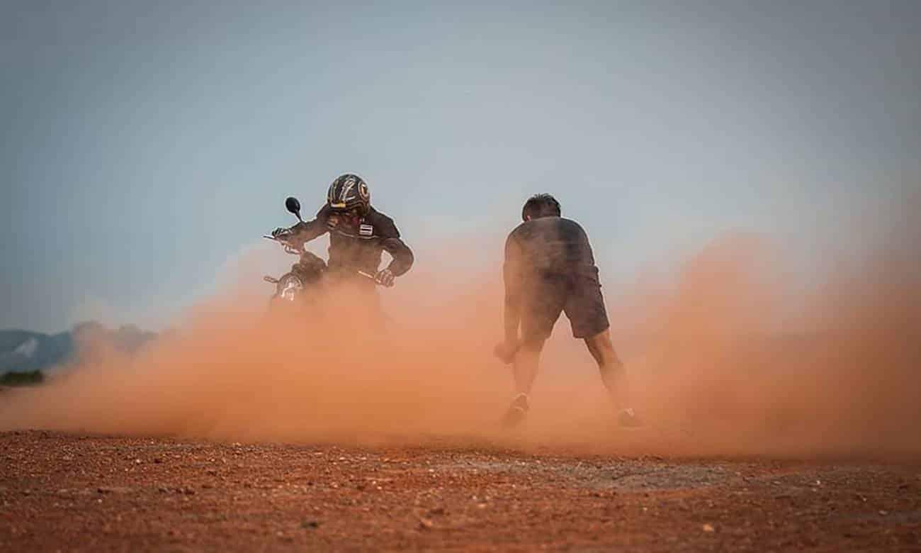 Moto e pessoa em meio a poeira